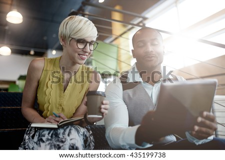Two creative millenial small business owners working on social media strategy using a digital tablet while sitting in staircase