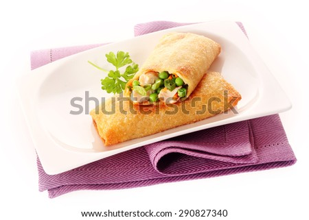 Two Crisp Fried Spring Rolls Filled with Fresh Vegetables on White Dish with Garnish and Purple Napkin - stock photo