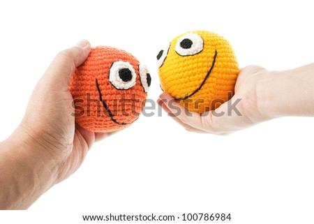 Two crochet smileys in woman and man hands looking to each other. Isolated on white background. - stock photo