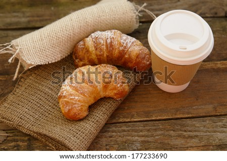 Two croissants and coffee-to-go in a rustic setting - stock photo