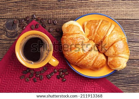 Two croissants and cup of coffee on wooden table. Top view