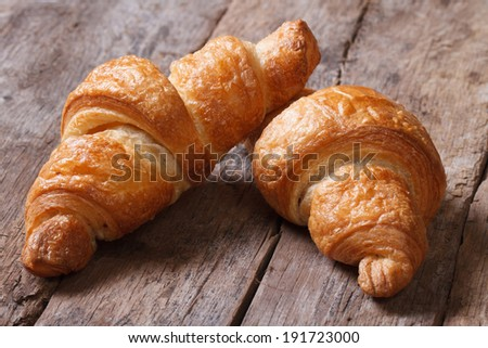 two croissants on an old wooden table closeup