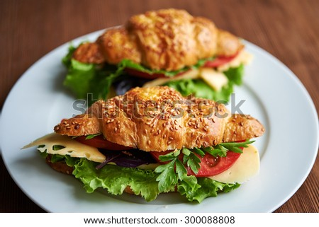 two croissants with tomatoes, cheese and lettuce - stock photo