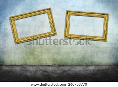 Two crooked golden frames on gray dirty wall - stock photo
