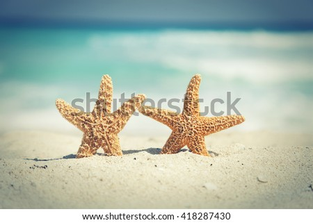 Two cross-processed starfish on the beach with ocean waves in background - stock photo