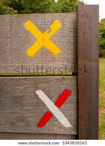 two crosses painted on a wooden barrier photographed in Auvergne. This crosses are hiking symbols.