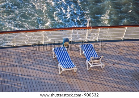Two cruise ship lounge chairs overlook the ocean - stock photo