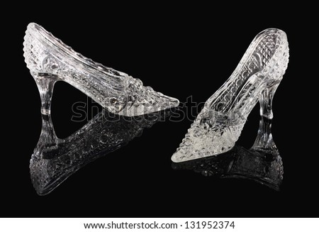 Two crystal shoes of the Cinderella stand on a black mirror - stock photo