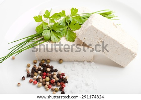 two cubes of raw tofu with spices on white plate - stock photo
