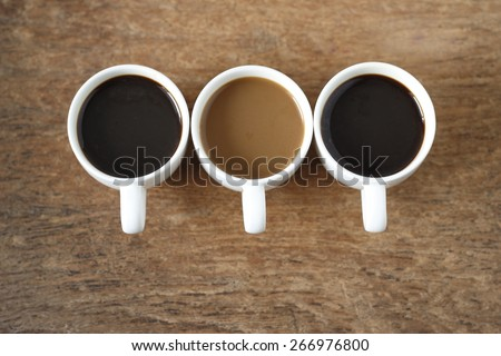 two cup of  hot black coffee, a cup of  instant coffee place on old wood background. three cup of coffee on old wood background. - stock photo
