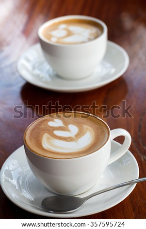 Two cup of latte coffee on wood table