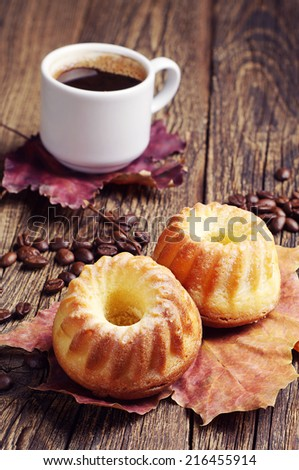 Two cupcake, cup of hot coffee and autumn leaves on wooden background - stock photo