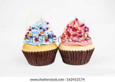 Two cupcake ornaments against a white background