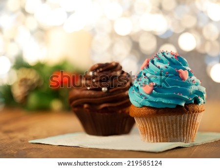 Two cupcakes - shallow DOF. Christmas lights in the background. - stock photo