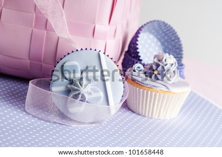 two cupcakes with empty cups on a lilac and pink setting - stock photo