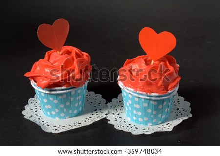 two cupcakes with red butter cream in blue polkadot cup. Romantic conceptual - stock photo