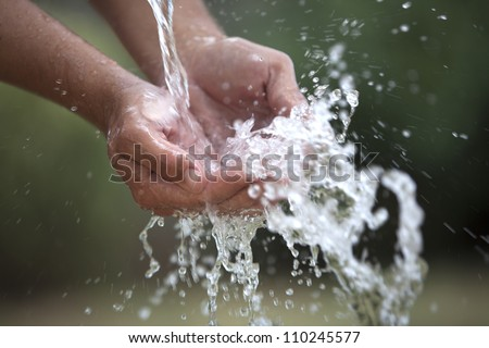 Two cupped hands feel the water spashing into them gently.