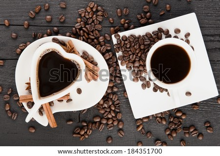 Two cups in heart shape of coffee with croissants and pieces of cinnamon - stock photo