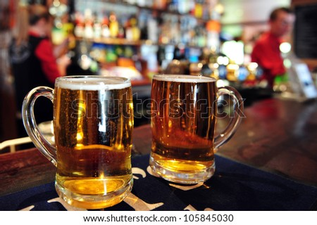 Two cups of beer in a pub in New Zealand. Concept photo of drinking beer and alcohol - stock photo