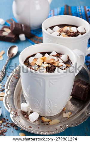 Two cups of chocolate almond milk with marshmallow and almond chips. Selective focus - stock photo