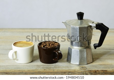 two cups of coffee and beans and percolator on wood - stock photo