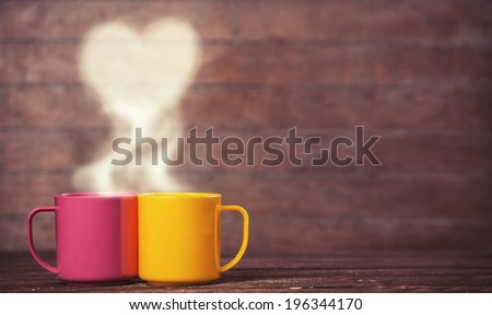 Two cups of coffee and heart shape on wooden background. - stock photo