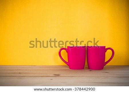 Two cups of coffee and stand together to be heart shape on yellow background. - stock photo