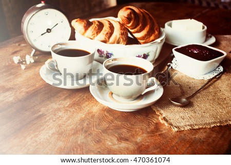 Two cups of coffee, croissants and an alarm clock. Breakfast for two. Old vintage photo