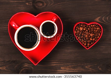 Two cups of coffee in the red heart, standing on black wooden table. Drinking coffee together on St. Valentine's day