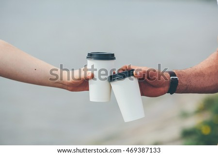 two cups of coffee in their hands against the background of the lake