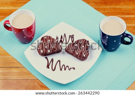 Two cups of coffee latte on the table. Sweet dessert in the form of heart. Red and blue cup. Cup, dessert on a plate, breakfast for two, romance, relationships. - stock photo