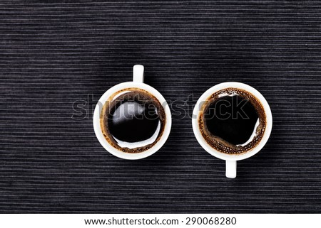 two cups of coffee on a black background - stock photo