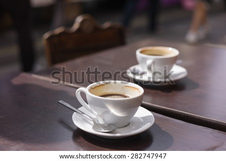 Two cups of coffee on a table outside in the street