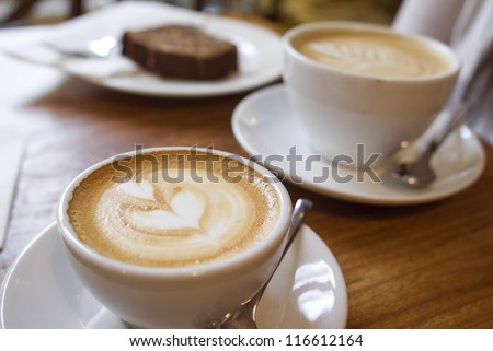 Two cups of coffee on the table, latte art - stock photo