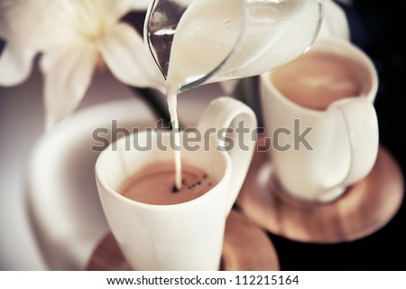 Two cups of coffee with decoration and poured milk - stock photo