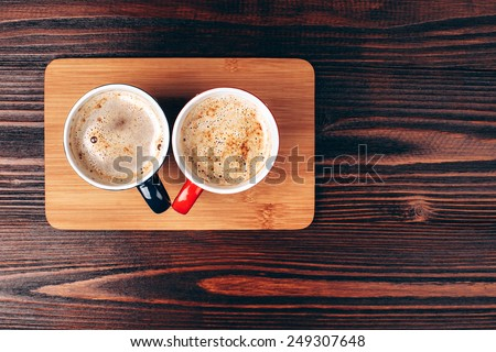 Two cups of coffee with foam standing on wooden board, on wooden table - stock photo