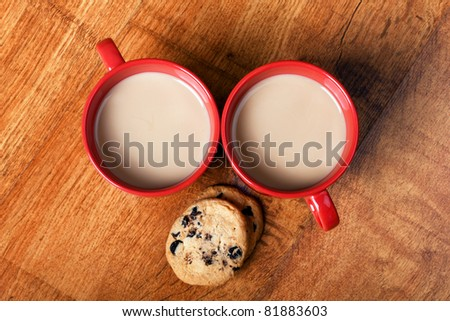Two cups of coffee with milk and chocolate cookies on the wooden surface - stock photo