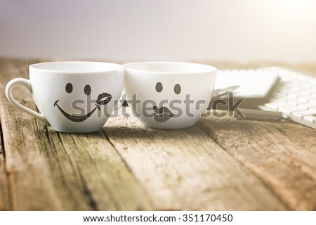 Two cups of coffee with smiley and kiss face on wooden table with keyboard and notebook. Toning photo - stock photo
