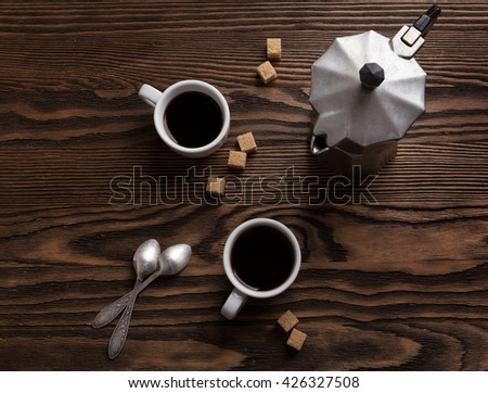 Two cups of espresso with pieces of cane sugar and Italian  coffee maker on wooden table.