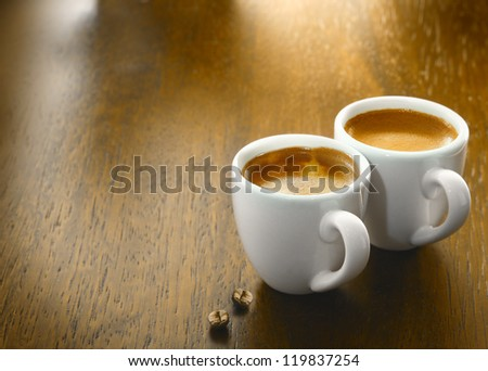 Two cups of freshly brewed espresso coffee with two single coffee beans on a textured wooden table top with copyspace - stock photo