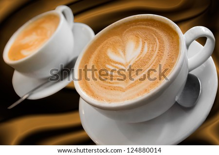 Two cups of gourmet coffee house cappuccino against a silky background - stock photo