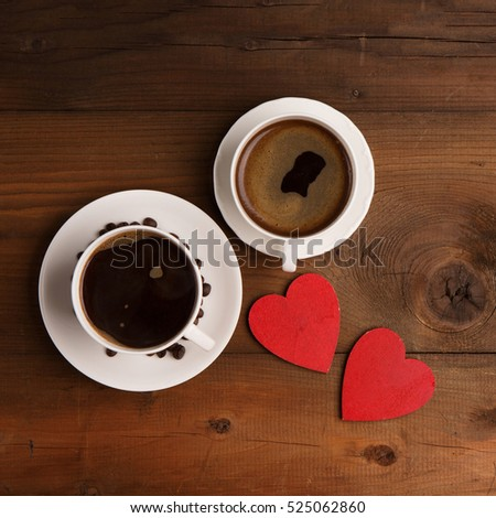 Two cups of hot coffee and red wooden hearts on rustic dark textured background. Valentine's day celebration concept, top view