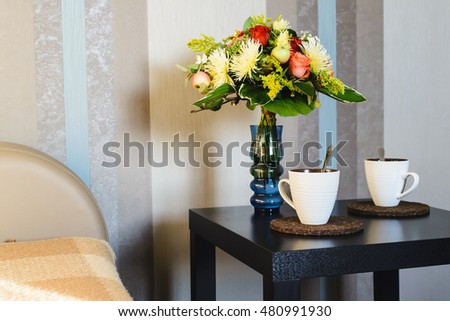 two cups of hot drink near bouquet of flowers in vase on table in apartment