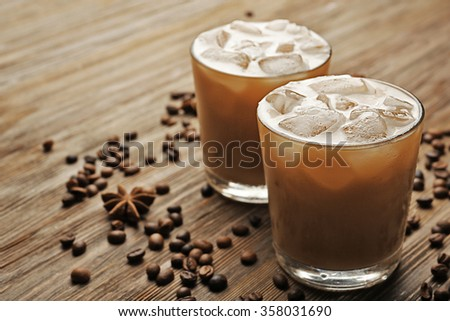 Two cups of ice coffee with coffee beans on wooden table - stock photo