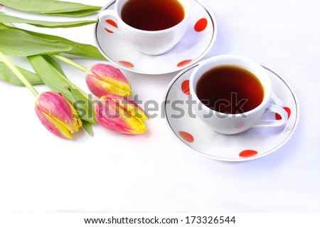 Two cups of tea and fresh red tulips on white background