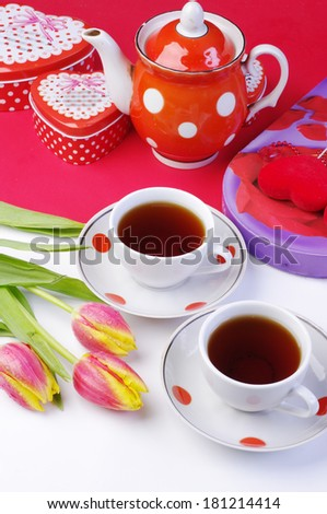 Two cups of tea, tulips and teapot - stock photo