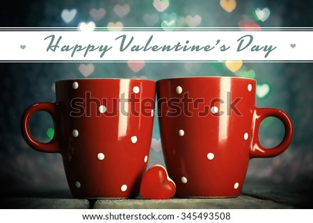 Two cups on table on bright lights background - stock photo