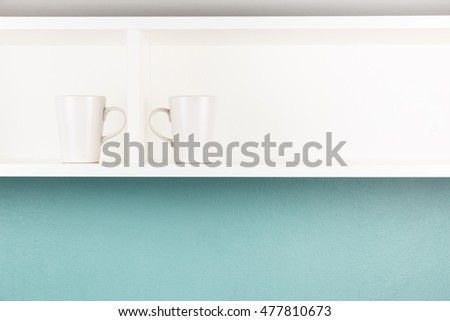 Two cups on white shelf