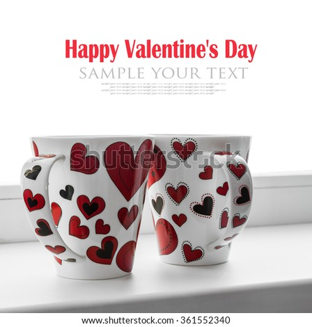 two cups with hearts on the screen isolated on white background. It can be used for Valentine's Day greetings - stock photo