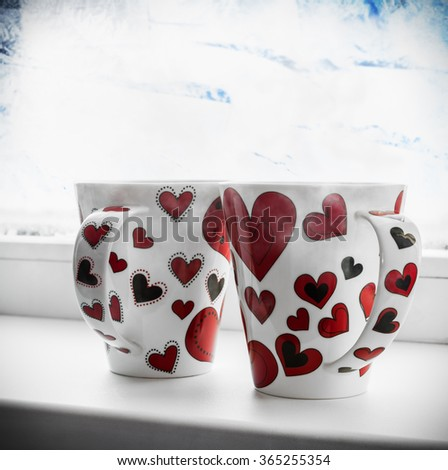 two cups with hearts on the window sill of a frozen window. It can be used for Valentine's Day greetings - stock photo